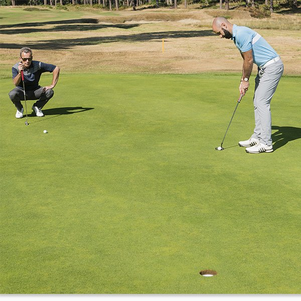 Golfer Lining Up a Putt During Playing Partner's Putt